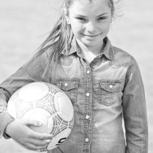 Tjej som håller i en fotboll