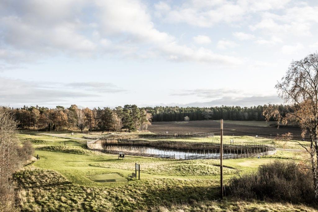 Golfbana med skog och sjö